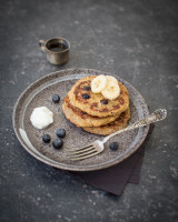 Three small pancakes toped with banana slices, on a grey plate with blueberries and a dollop of yoghurt