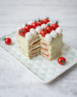 Toast layered cake with mozzarella and cherry tomaotes on tray next to a cake server