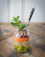 Jar with quinoa, cucumber, grated carrots, pomegranate seeds and pistachios