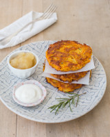 Plate with three potato pancakes, a mini apple compote bowl and mini bowl of cream