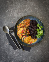 Baked aubergine slices in yellow sauce with black rice and cilantro, dressed in a black bowl with a dark background