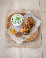 Curried chicken drumsticks with cucumber salad on a wooden plate