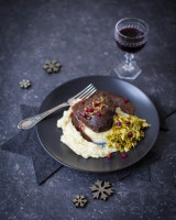 Plate of pure and slow-cooked beef cheeks with some winter decoration in a dark setting