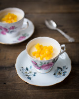 Two coffee cups filled with Indian kulfi and mango cubes