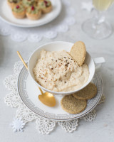 Cup of hummus dip with some oatmeal cookies with another plate of fingerfood and a glass of champagne in the background