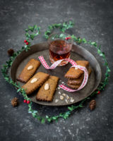 German cookies on a dark plate next to a mulled wine glass placed on a dark background decorated with acrons