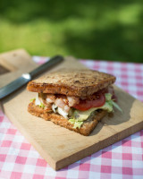 Bacon, tomato, salad sandwich on a wooden board at a picnic table