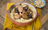 Tagine with couscous, almonds and prunes on a yellow cloth