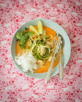 Bowl with yellow curry, chicken, cashew nuts, zucchini noodles, cilantro and lemon wedges on a pink background with white bunnies