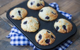 Muffin tin with six blueberry pastries on a wooden background