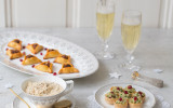 Three plates of festive fingerfood with champagne glasses and winter decoration