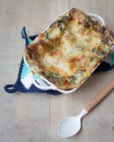 Lasagna placed on a table on a blue and white table cloth beside a wooden spoon